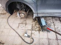 Llave neum?tica con las nueces del neum?tico de coche en del piso el gato concreto del coche a un lado y un pedazo de metal aherr fotos de archivo libres de regalías