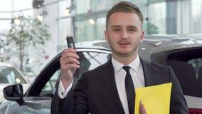 Llave profesional del coche de la tenencia del vendedor de coches, mirando a la cámara con confianza metrajes