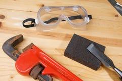 Llave roja con los anteojos de seguridad en el banco de trabajo Imagen de archivo