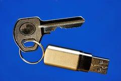Llave y llavero pendiente de memoria USB del ordenador en fondo azul fotografía de archivo