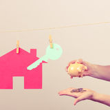 Llave y mano de la casa con el piggybank Fotos de archivo
