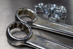 Llave y nueces en una tabla del metal en un taller Accesorios para el mechaics para las reparaciones mecánicas de menor importanc foto de archivo
