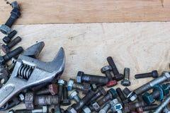 Llave y tornillos de llave inglesa en el fondo de madera Fotografía de archivo libre de regalías