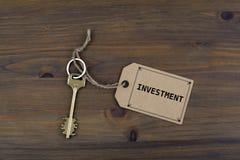Llave y una nota sobre una tabla de madera con el texto - inversión Imágenes de archivo libres de regalías