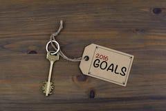 Llave y una nota sobre una tabla de madera con el texto - 2016 metas Nuevo Yea Fotos de archivo libres de regalías