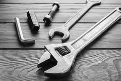 Llaves ajustables, llaves inglesas en textura de madera Foto de archivo