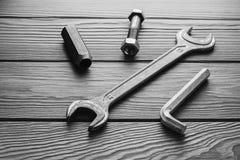 Llaves ajustables, llaves inglesas en textura de madera Foto de archivo libre de regalías