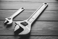 Llaves ajustables, llaves inglesas en textura de madera Imagen de archivo libre de regalías