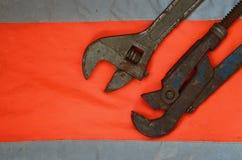 Llaves ajustables y de tubo contra la perspectiva de una camisa anaranjada del trabajador de la señal Todavía vida asociada a la  Foto de archivo