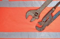 Llaves ajustables y de tubo contra la perspectiva de una camisa anaranjada del trabajador de la señal Todavía vida asociada a la  Fotos de archivo libres de regalías