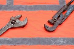 Llaves ajustables y de tubo contra la perspectiva de una camisa anaranjada del trabajador de la señal Todavía vida asociada a la  Imagen de archivo libre de regalías