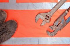 Llaves ajustables y de tubo contra la perspectiva de una camisa anaranjada del trabajador de la señal Todavía vida asociada a la  Imágenes de archivo libres de regalías