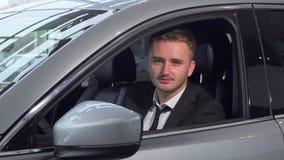 Llaves alegres del coche de la tenencia del hombre de negocios que se sientan en un nuevo auto en la representación almacen de metraje de vídeo