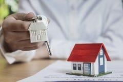 Llaves de entrega de la casa del agente de la propiedad inmobiliaria imágenes de archivo libres de regalías