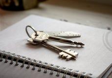 Llaves de la casa en el cuaderno Fotos de archivo libres de regalías