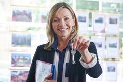 Llaves de In Office Holding del agente de la propiedad inmobiliaria a la propiedad Foto de archivo libre de regalías