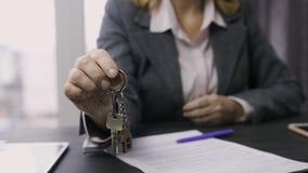 Llaves de ofrecimiento del midsection del agente de la propiedad inmobiliaria a la cámara metrajes