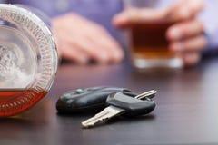 Llaves del coche cerca de la botella de alcohol Imágenes de archivo libres de regalías