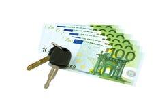 Llaves del coche en billetes de banco euro Foto de archivo