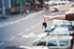Llaves del coche en la mano del ` s de la muchacha contra el camino Imagen de archivo