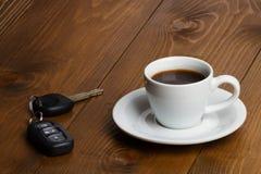 Llaves del coche y taza de café Fotografía de archivo libre de regalías