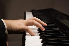 Llaves del piano y mano humana Foto de archivo libre de regalías