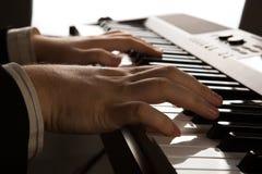 Llaves del piano y manos humanas Imagenes de archivo