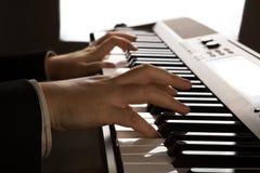 Llaves del piano y manos humanas Fotos de archivo