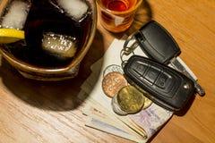 Llaves del whisky, del cóctel, del dinero y del coche en la barra Imagenes de archivo