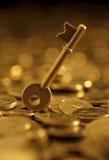 Llaves en apilado de monedas de oro Fotografía de archivo libre de regalías