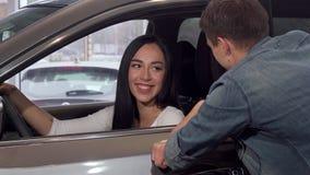 Llaves hermosas del coche de la demostración de la mujer a la cámara, sentándose en nuevo auto en la representación almacen de video