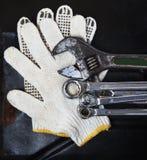 Llaves inglesas de las llaves que sondean y guante del mecánico en la parte posterior oscura del metal Imagenes de archivo