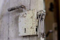 Llaves a la puerta principal de la casa Diversos accesorios necesarios Foto de archivo