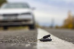 Llaves perdidas del coche que mienten en el camino, en un fondo borroso con efecto del bokeh fotografía de archivo