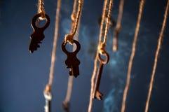 Llaves que cuelgan en una secuencia Fume el fondo Foco selectivo Foto de archivo libre de regalías