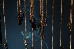 Llaves que cuelgan en una secuencia Fume el fondo Foco selectivo Fotos de archivo libres de regalías