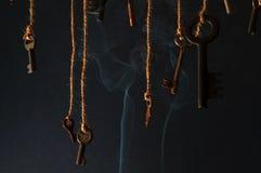 Llaves que cuelgan en una secuencia Fume el fondo Foco selectivo Imagen de archivo libre de regalías