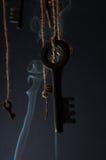 Llaves que cuelgan en una secuencia Fume el fondo Foco selectivo Imagenes de archivo