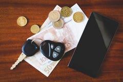 Llaves, teléfono y dinero del coche Fotos de archivo libres de regalías