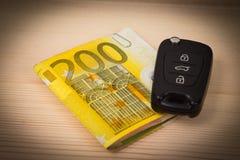 Llaves y dinero del coche en la tabla Fotos de archivo