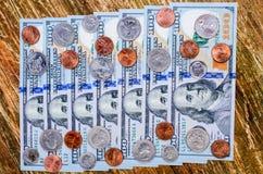 Lle banconote di cento dollari e di molte monete Fotografie Stock
