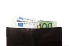 Lle banconote di cento euro che attaccano dal portafoglio nero, sul briciolo Immagini Stock Libere da Diritti