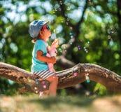 Lle bolle di un di anni sapone di salto della bambina nel parco di estate Fotografie Stock Libere da Diritti