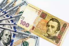 Lle bugie di un hryvnia della fattura cento sul fan fuori sparso cento banconote in dollari su un fondo bianco Immagini Stock Libere da Diritti