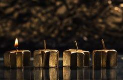 Lle candele dorate di un arrivo accese con il fondo del bokeh Fotografia Stock Libera da Diritti