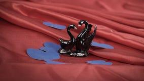 Lle cifre di due cigni neri su un fondo rosso fotografia stock