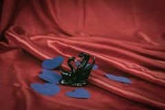 Lle cifre di due cigni neri su un fondo rosso fotografia stock libera da diritti