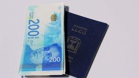 Lle fatture di soldi israeliane giranti dello shekel 200 e del passaporto israeliano - ciclo senza cuciture di vista superiore stock footage