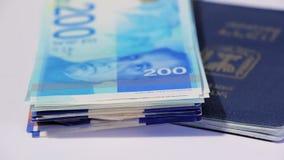 Lle fatture di soldi israeliane giranti dello shekel 200 e del passaporto israeliano - ciclo senza cuciture di vista superiore archivi video