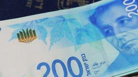 Lle fatture di soldi israeliane giranti dello shekel 200 e del passaporto israeliano - vista superiore stock footage